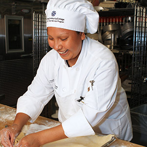Pima Community College culinary program student wearing chef's jacket and working in kitchen